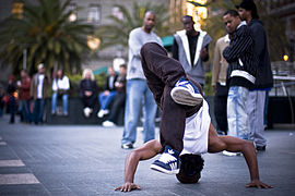 Five young men in the far background watch an African-American b-boy dance in a public plaza.