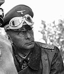 male in German field uniform wearing a peaked cap with goggles resting above the peak