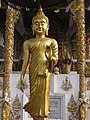 Beautiful gold Buddha in a walking pose (14717028636).jpg