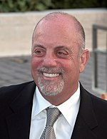 An upper body shot of a man wearing a shirt, suit and tie. He is balding and his smiling mouth is framed by a white goatee beard.