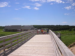 A boardwalk on Staten Island, with the Verrazano-Narrows Bridge in background.