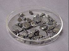 Several dozen small angular stone like shapes, grey in colour with scattered silver flecks and highlights.