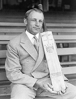 Cricketer Donald Bradman sits on a bench in a sports stadium and displays a cricket bat with his brand name on it. He wears a 1940s-style double-breasted suit and has his hair parted and slicked back with haircream, and is smiling.