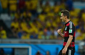 Klose pulling his arm towards himself in a goal celebration. He is wearing a red and black hooped kit. Fans in yellow Brazil jerseys are sat in the background.
