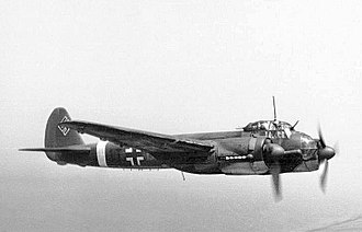 A twin engine propeller powered aircraft in flight and viewed from the right side. The aircraft bears multiple markings including a black and white cross on its side and swastika on the tail fin.