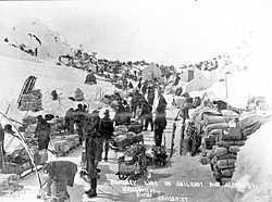 Klondikers and their supplies at US-Canadian border line on Chilkoot Pass, 1898