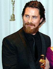 Christian Bale is smiling to his right.