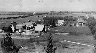 Orange, California - View of the early rural farm community in the town of Orange. A railroad train can be seen on the left.