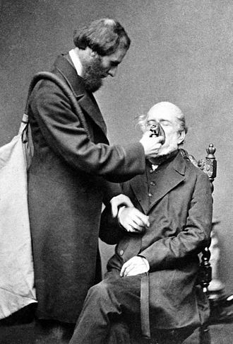 Joseph Thomas Clover - Posed photograph of Joseph Clover demonstrating his Chloroform apparatus on his father John Wright Clover in 1862
