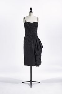 A black cocktail dress with spaghetti straps on a mannequin.
