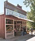 Photograph of a historic store, the Pioneer Emporium, in the Columbia Historic District. The building sports a tall false front, and several visitors stand in the shade of an awning.