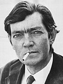 Head shot of a dark haired man in a suit and tie with a cigarette in his mouth. He is looking at the camera quizzically.