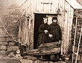 Couple in front of their house, 1890.jpg