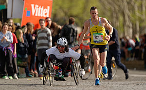 Paris Marathon - A runner gives a friendly tap on the shoulder to a wheelchair racer