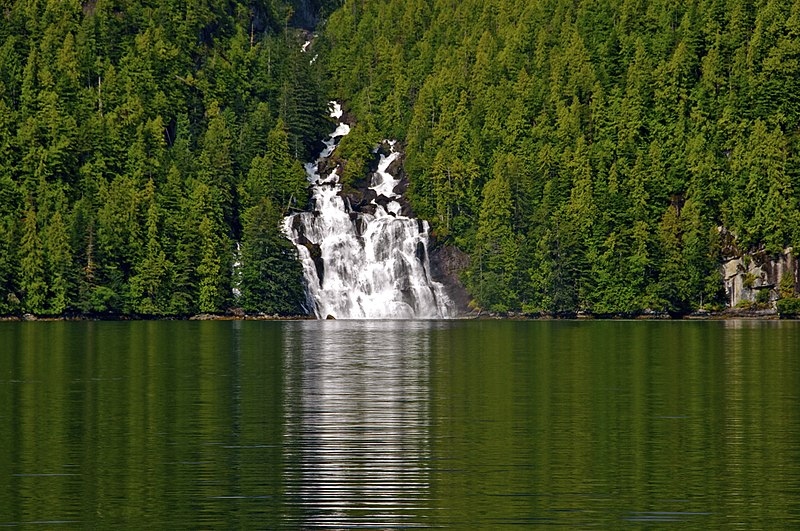 Lizette Falls amidst the forests falling into a lake/fjord in the great bear rainforest of British Columbia