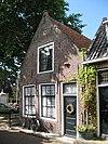 foto van Eenvoudig bakstenen huis met zadeldak. Puntgevel. Oorspronkelijke deur. Beneden 2 negenruiters; in de top een zestienruiter