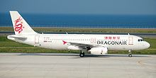 An aircraft painted in white, with a red dragon on its tail and the name Dragonair in both English and Traditional Chinese on the fuselage, taxiing on the taxiway