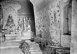 Mogao Caves - Picture of Cave 16, by Aurel Stein in 1907, with manuscripts piled up beside the entrance to Cave 17, the Library Cave, which is to the right in this picture.