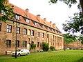 Budynek Muzeum Archeologiczno-Historycznego w Elblągu, mieszczący się na terenie Podzamcza dawnego Zamku Krzyżackiego. Na muzealnym dziedzińcu, uważanym za dawną strefę gospodarczą krzyżackiego zamku, odnalezione zostały drewniane konstrukcje, które mogą być pozostałością po warowni wzniesionej w XIII wieku przez Krzyżaków. Źródło: Wiki Commons, autor: Hans Weingartz, lic. CC-BY-SA-2.0.