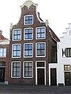 foto van Hoog pand met twee verdiepingen en klokvormige top onder zadeldak met versierde aanzetstukken, deklijst en bekroning