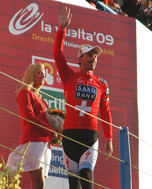Fabian Cancellara -  alt=A man walking across a stage while waving and wearing a red jersey