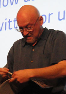 A caucasian, bald man wearing glasses and a dark shirt: He looks down at a book and pen held in his hands.