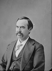 A man with dark hair and a mustache wearing a dark jacket and vest, light tie, and white shirt
