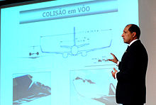 A standing middle-aged man wearing a suit, points to a screen showing a diagram of the two aircraft colliding by clipping each other's wings.