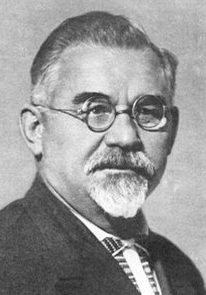 Central Committee elected by the 13th Congress of the All-Union Communist Party (Bolsheviks) - a bearded man with wavy hair, wearing glasses and what seems to be a suit, a white tie, and a black and white dotted shirt