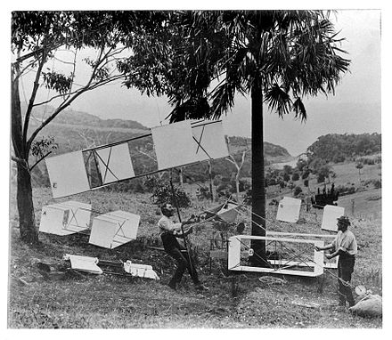 Lawrence Hargrave (seated) and Swain demonstrate the manlift kites (labelled A, B, D, & E), sling seat and spring balance in the parkland behind Stanwell Park beach, November 1894 Hargrave-demo.jpg
