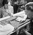 In the workrooms of the fashion designer Norman Hartnell in London, two women apply studs by hand to the belt and shoulder pieces of an afternoon frock, 1944. D23066.jpg