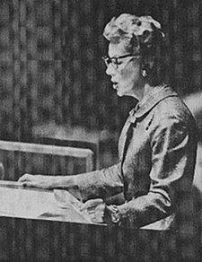Monochrome photograph of a bespectacled, short-haired woman in a suit jacket reading from papers at a podium