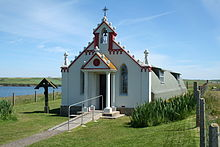 A small chapel sits in green fields under a blue sky. A body of water lies to the left. The front of the building is painted red and white and is decorated with colonnades and a small bell tower. By contrast the main part of the building is painted grey and has a curved exterior reminiscent of a Nissen hut.