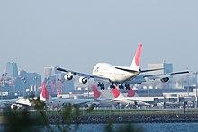 Pesawat sedang mendarat dengan pemandangan terminal bandara di latar belakang