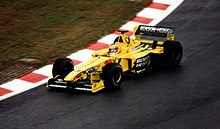 A figure, wearing a helmet with a white, red, yellow and blue design, is driving a Formula One that is of a yellow and black colour scheme.