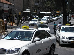 Israeli white taxis traveling the noontime str...