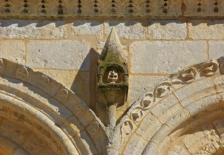Small column ended with a pinnacle containing a grotesque head: detail of the facade, church of Jonzac, Charente-Maritime, France.