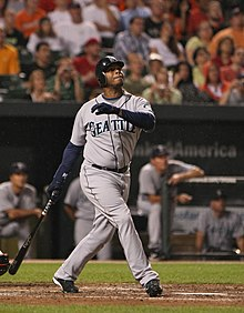 "An dark skinned man wearing a gray baseball uniform with ""SEATTLE"" on the chest stands holding a baseball bat in his right hand as if having just taken a left-handed swing."