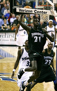 fb7454bad Kevin Garnett wearing black Timberwolves jersey as he jumps with the  basketball towards the basket.