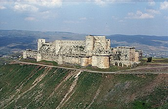 An enormous castle with encircling walls, on a rise in barren country with distant mountains.