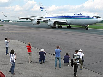 Aircraft spotting - A group of spotters at Domodedovo International Airport taking photos of a KrasAir Ilyushin Il-96-300 in 2008.