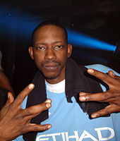 An image of a man wearing blue shirt and flashing a hand sign to the camera.