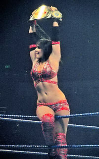 A dark-haired, tanned Caucasian female straddles the top rope of a wrestling ring with blue ropes. She is wearing a red patterned crop top, and matching shorts and kneepads. She is holding a wrestling championship above her head with both hands.