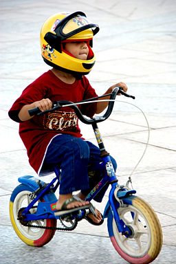 Little boy without training wheels with helmet and sandals