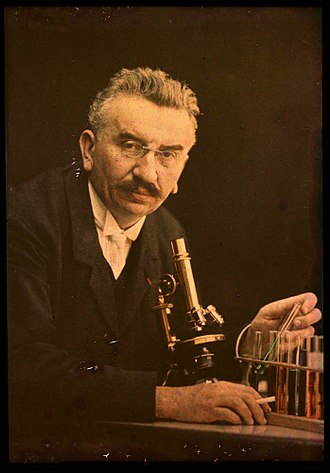 Test tube - Louis Lumière with a microscope and some test tubes.