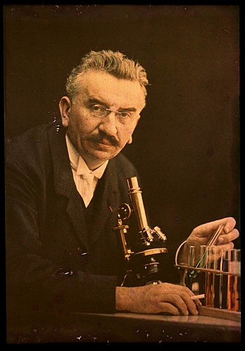 Louis Lumiere with microscope and test tubes, ...