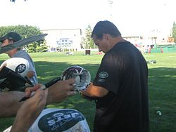 Waist up photograph from the side of Mangini wearing a green New York Jets t-shirt and signing an autograph
