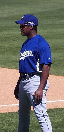 A dark-skinned man in a blue baseball jersey and cap and gray baseball pants wearing sunglasses and standing on a baseball field