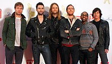 Five Caucasian men and one African-American man, all wearing jackets, stand in front of a backdrop featuring various company logos.