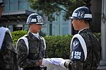 Members of the Republic of Korea air force air police fold the Korean flag (USAF photo 140516-F-FM358-093).jpg